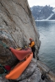 Lashing the kayaks to the base of 'Blueberry Buttress', East Greenland