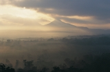 Volcanic peaks, dawn, mist and smoke
